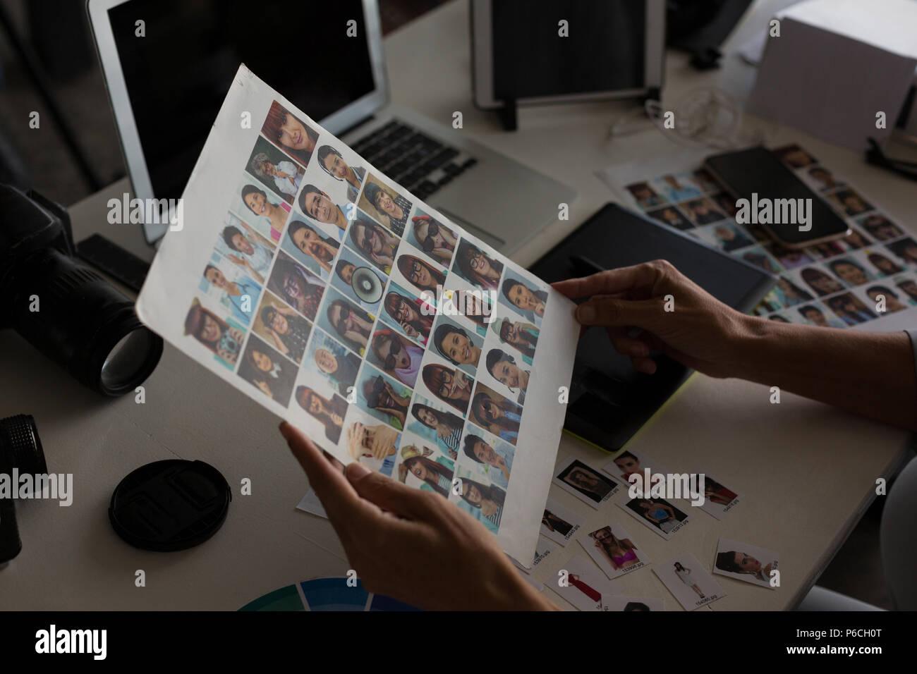 Femme graphic designer holding photograph Banque D'Images