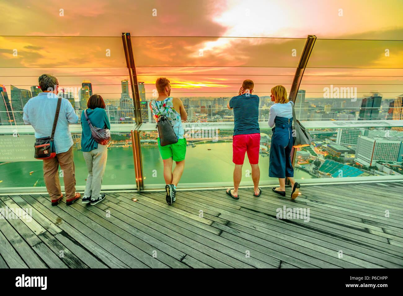 Singapour - 3 mai 2018: les touristes à la recherche d'une vue panoramique à partir de la plate-forme d'observation Skypark de Marina Bay Sands Hotel and Casino. Financial District skyline sur arrière-plan. Tourné au coucher du soleil. Banque D'Images