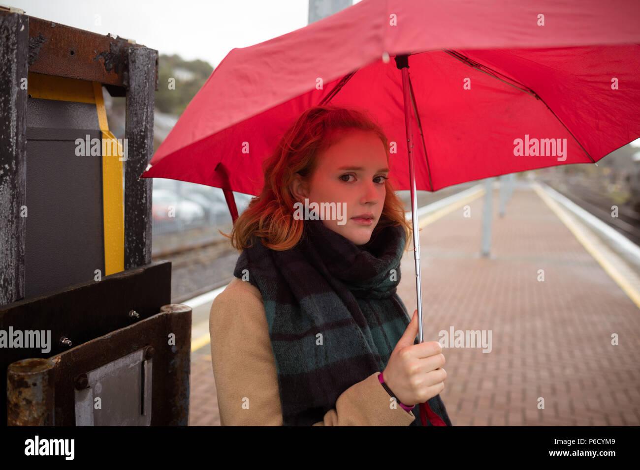 Jeune femme avec parapluie en attente de train sur la plate-forme Banque D'Images