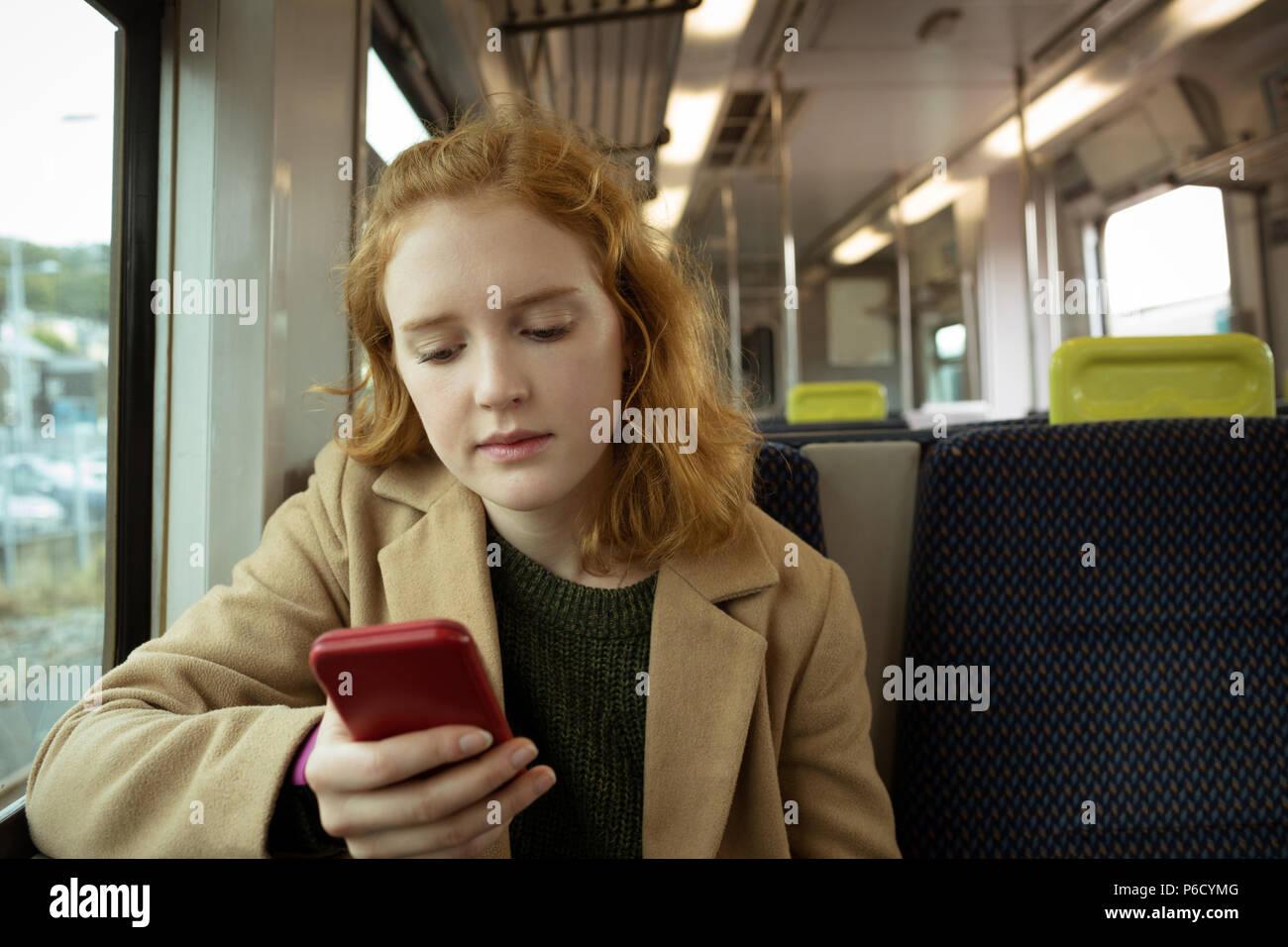 Cheveux rouge jeune femme en utilisant son mobile Banque D'Images