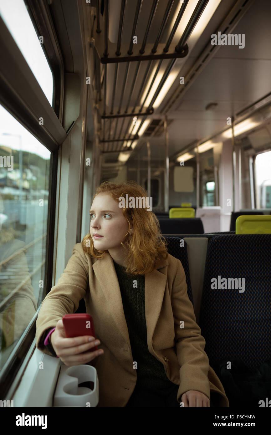 Red hair woman tout en utilisant son mobile Banque D'Images