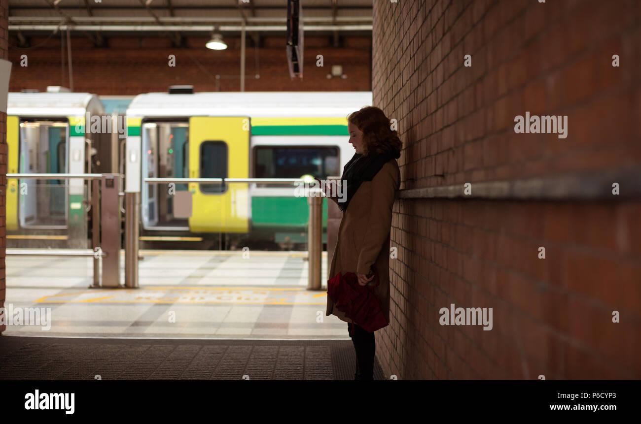 Woman using mobile phone à la gare Banque D'Images