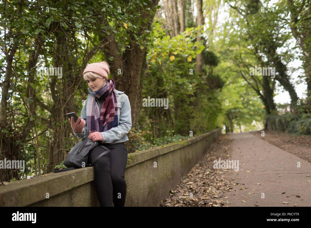 Jeune femme dans des vêtements chauds en utilisant son téléphone portable Banque D'Images
