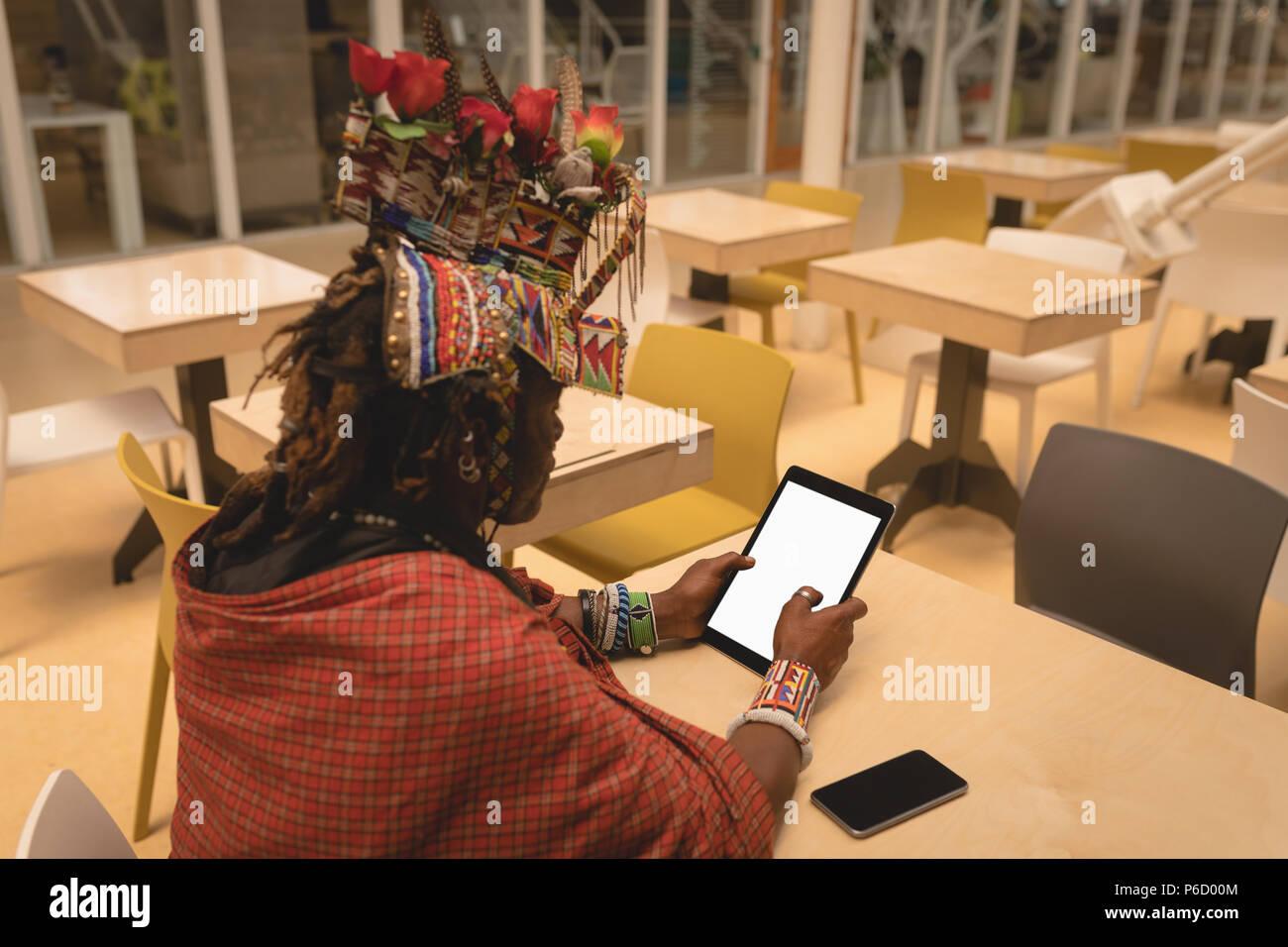 L'homme en costume traditionnel massaï using digital tablet Banque D'Images