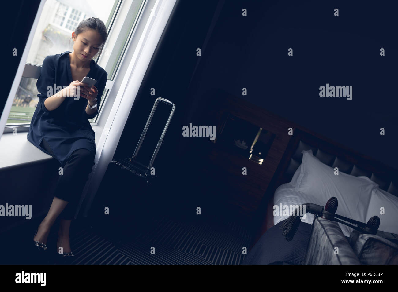 Woman using mobile phone in hotel room Banque D'Images