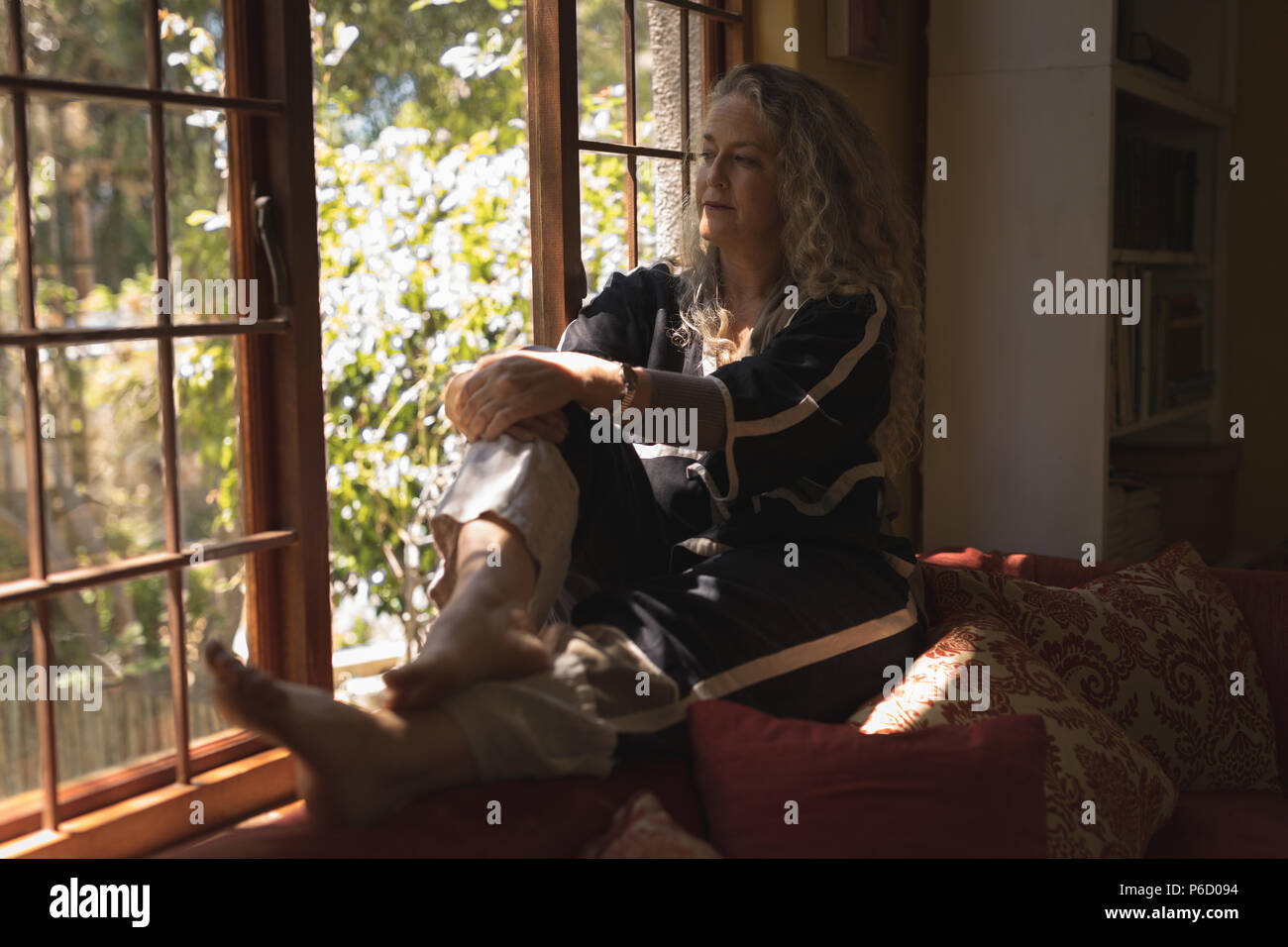 Thoughtful mature woman sitting on windowsill Banque D'Images