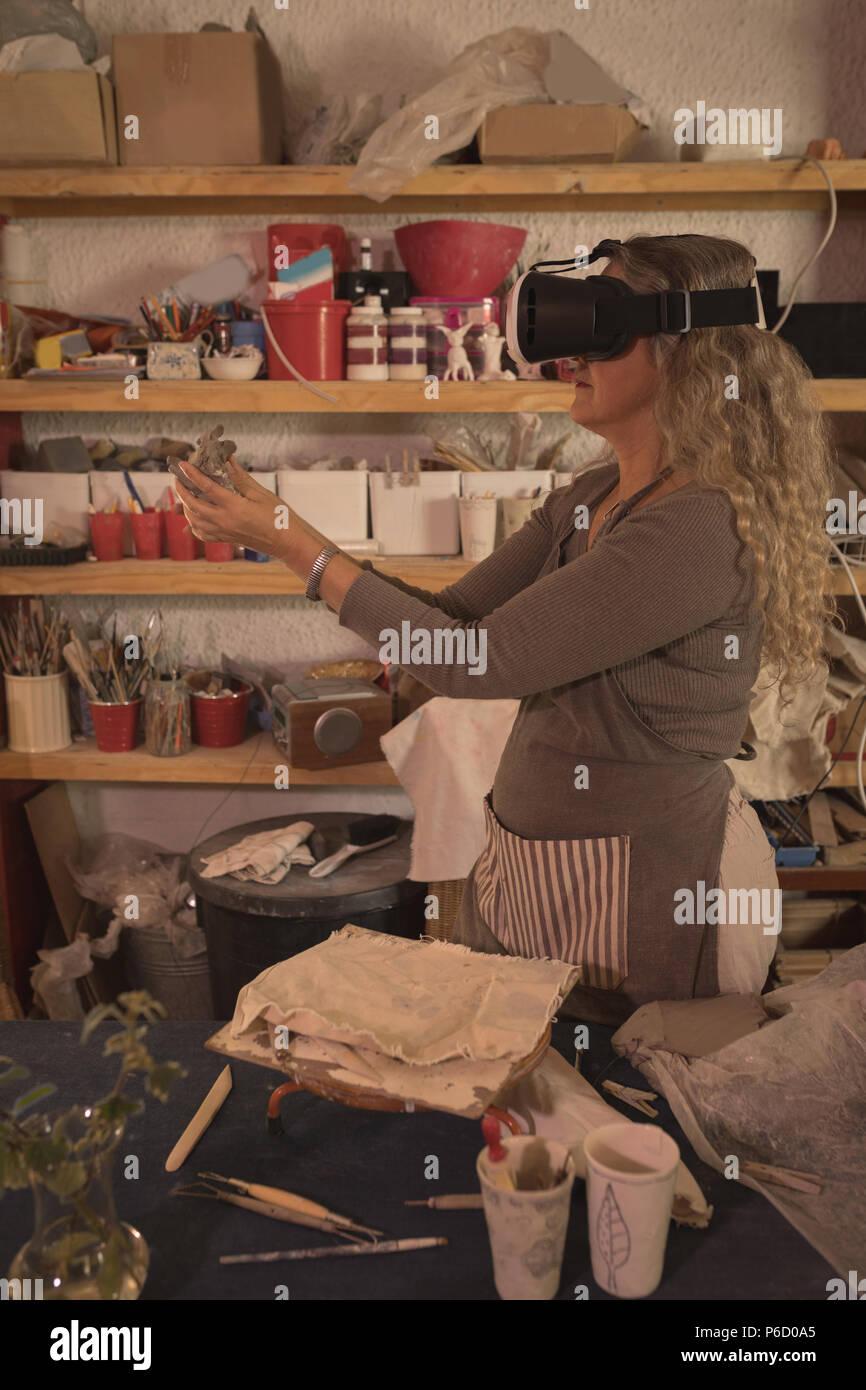 Potter femelle à l'aide de casque de réalité virtuelle Photo Stock
