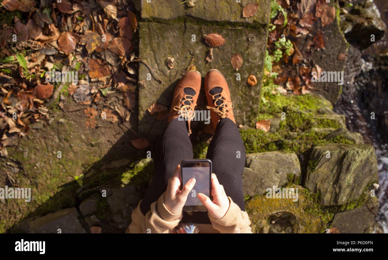 La section basse de woman using mobile phone Banque D'Images