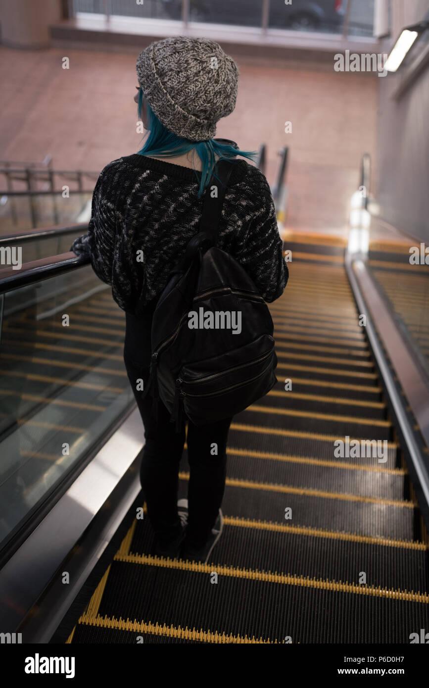 Femme en descente d'un escalier mécanique à la station Banque D'Images