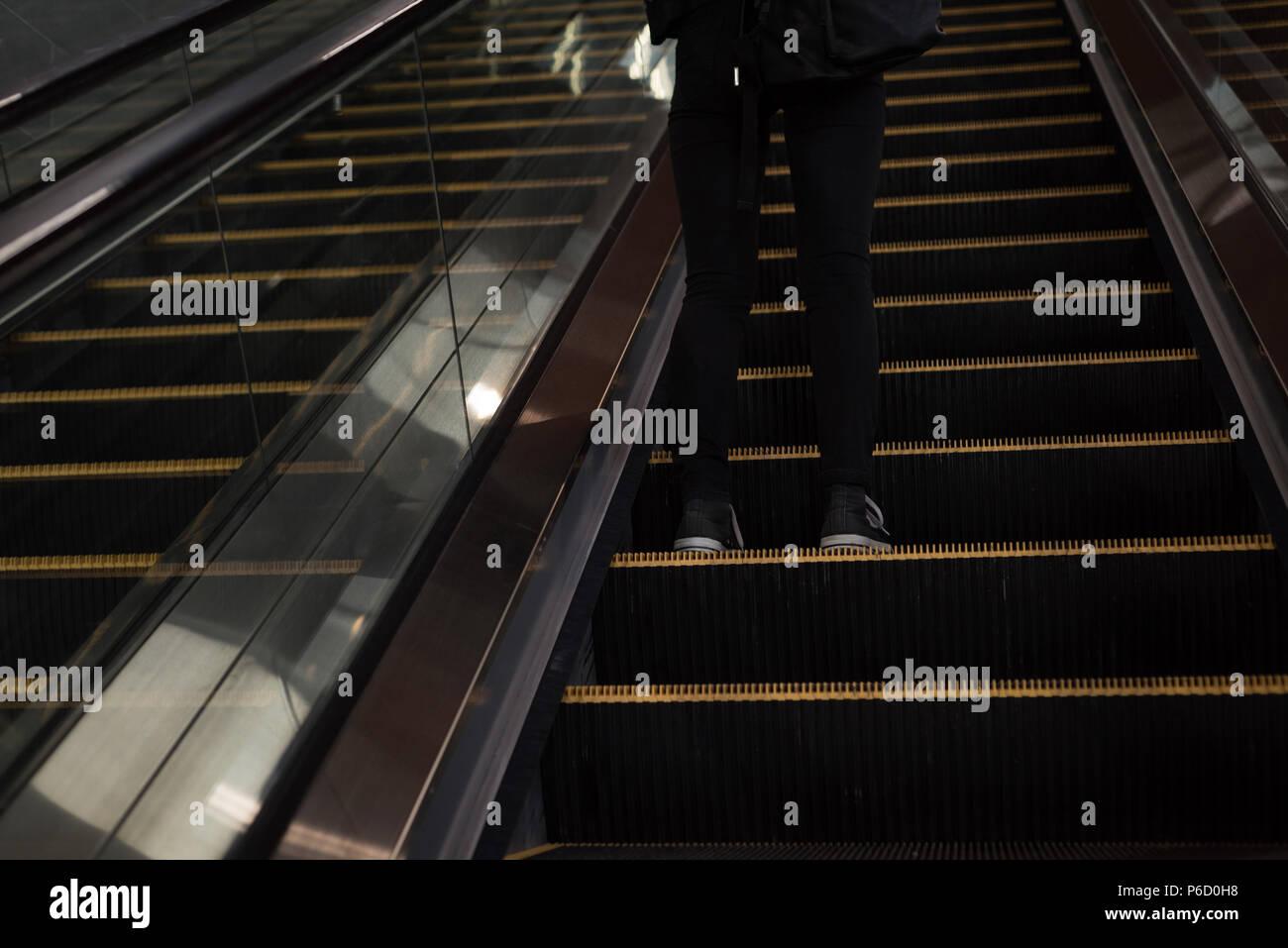 Femme debout d'un escalier mécanique à la station Banque D'Images