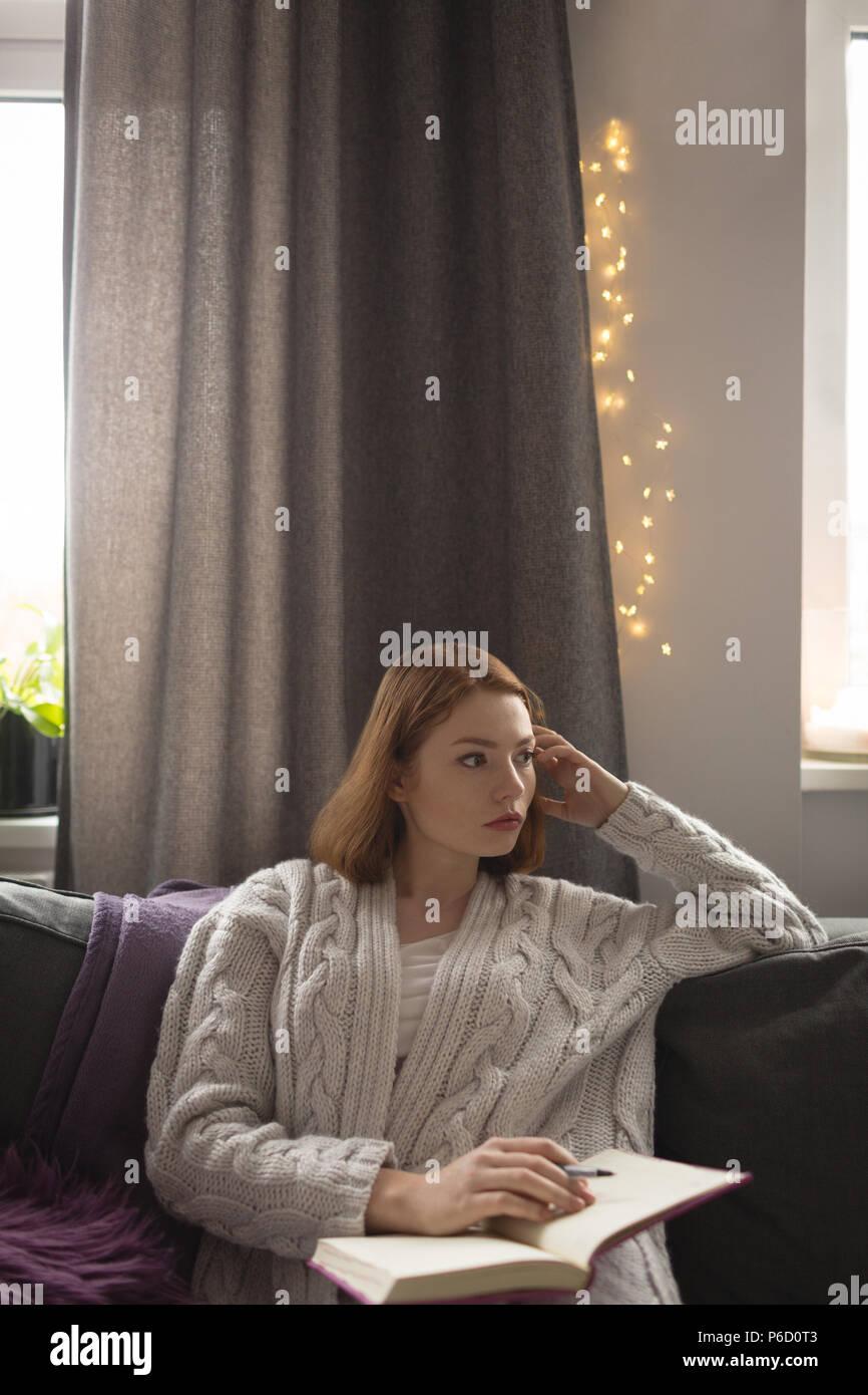 Femme écrivant sur un journal dans la salle de séjour à la maison Banque D'Images