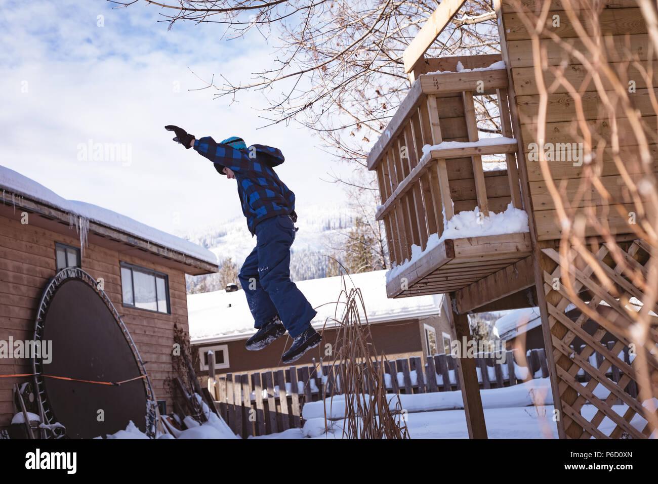 Garçon jouant dans la neige aire de jeux couverte Banque D'Images