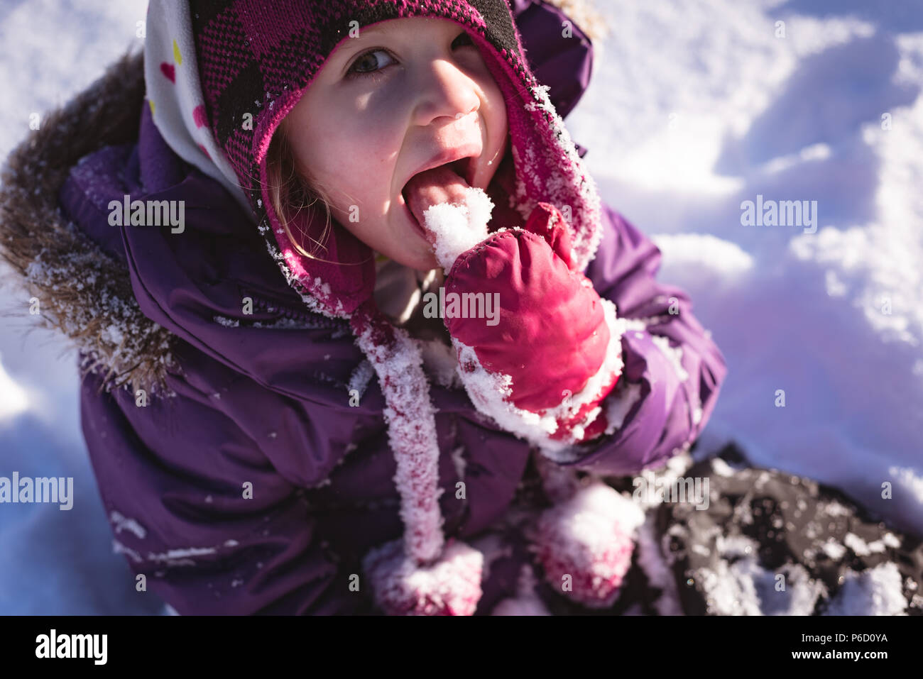 Portrait of cute girl licking snow Banque D'Images