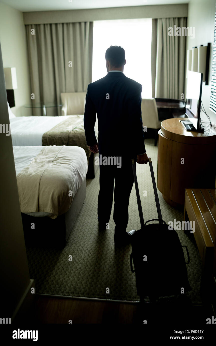 Businessman standing with luggage in hotel room Banque D'Images