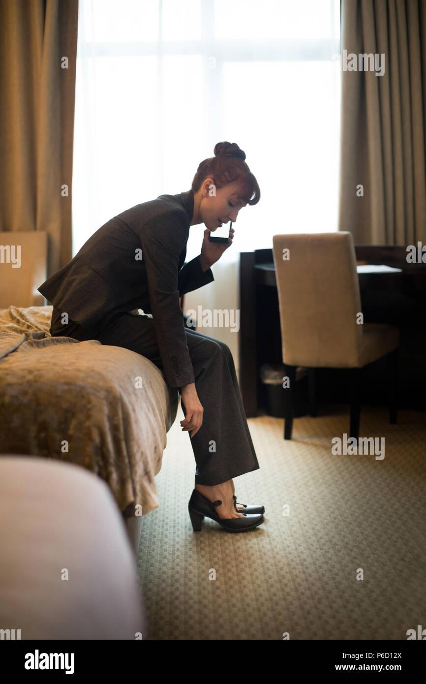 Businesswoman talking on mobile phone tout en portant des chaussures Photo Stock