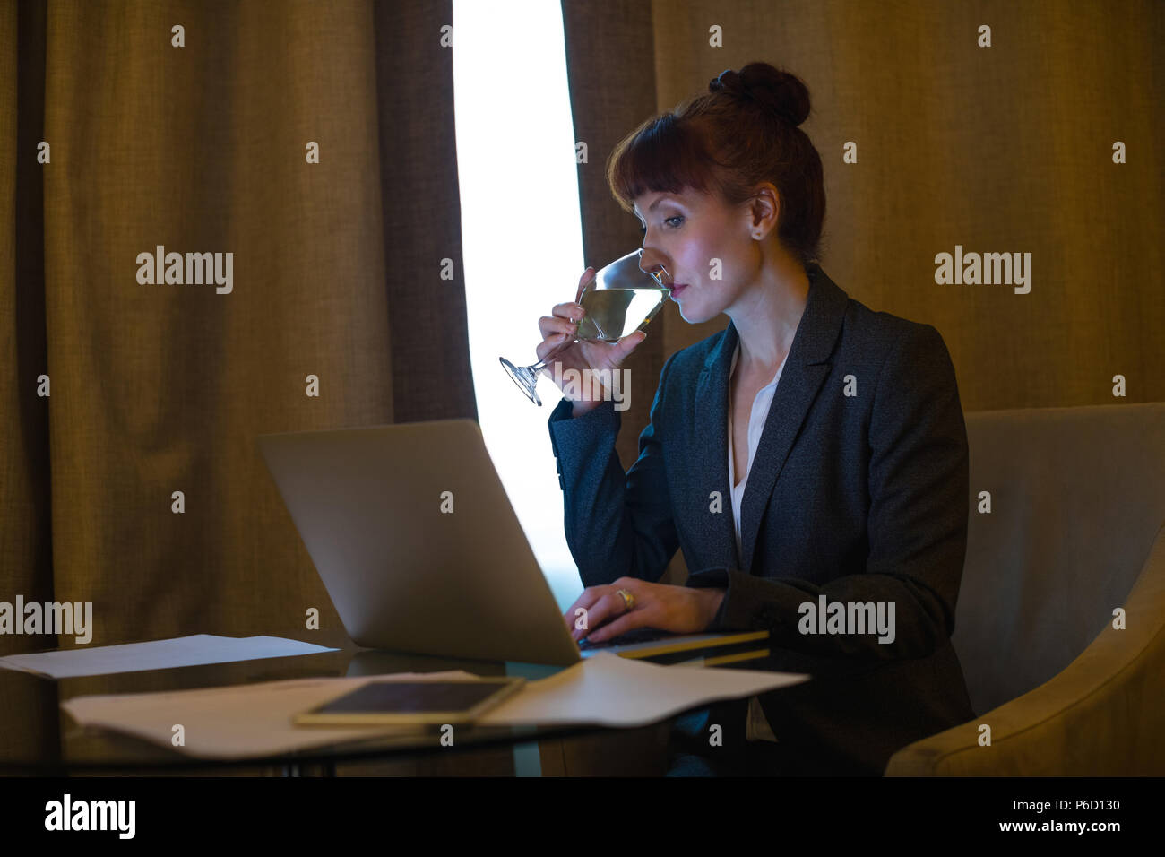 Businesswoman using laptop while having wine Photo Stock