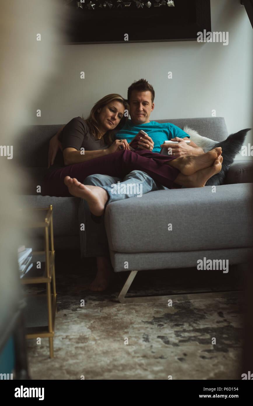 Couple à l'aide de téléphone mobile et tablette numérique dans la salle de séjour Banque D'Images