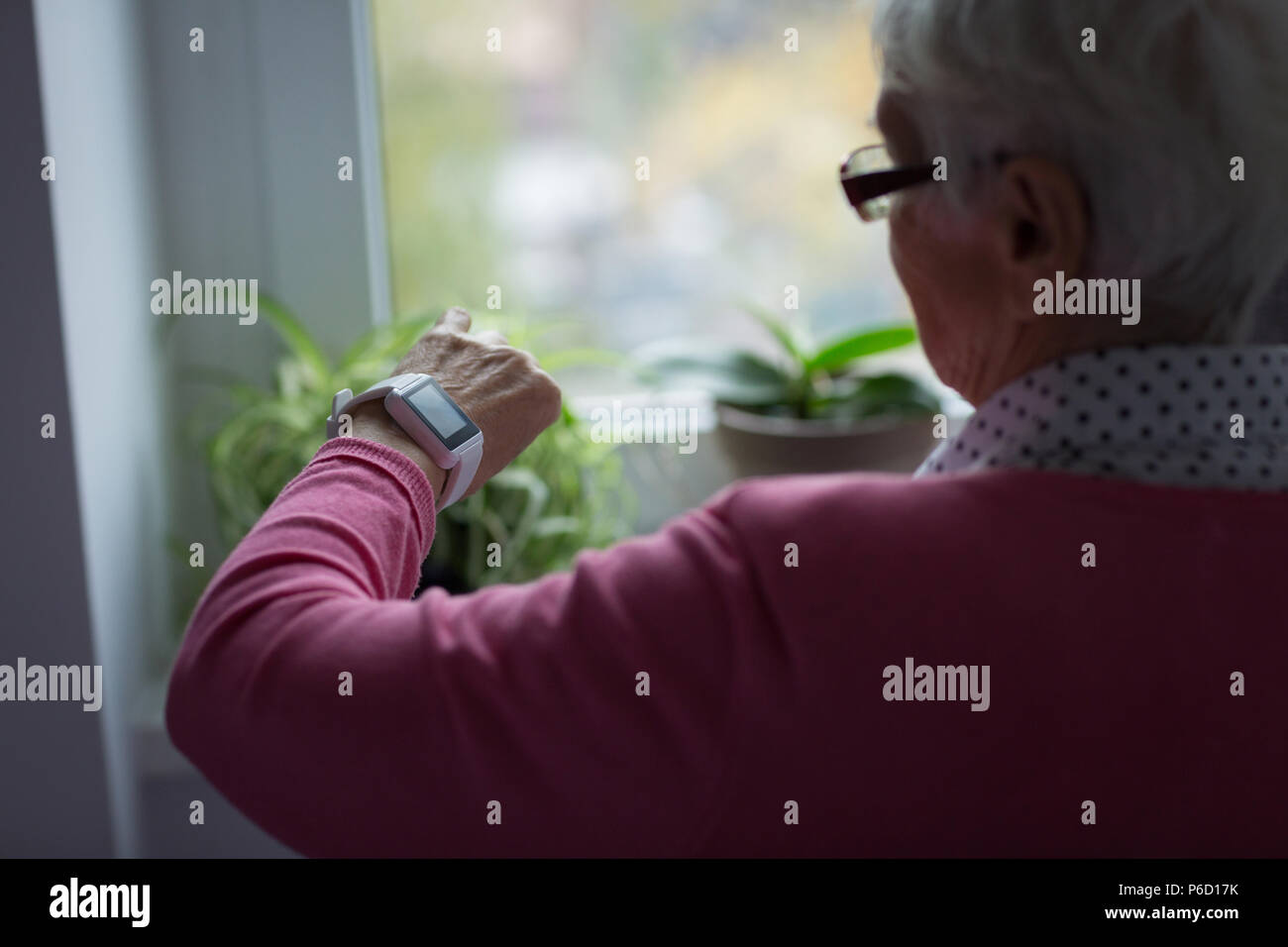 Senior woman contrôler le temps sur sa montre Banque D'Images