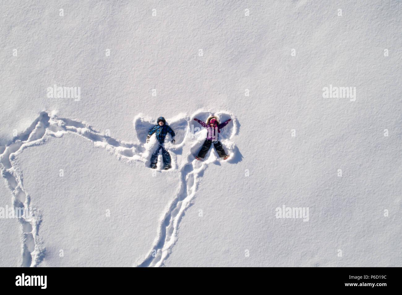 Les enfants se trouvant sur la neige et la neige qui forme l'ange Banque D'Images