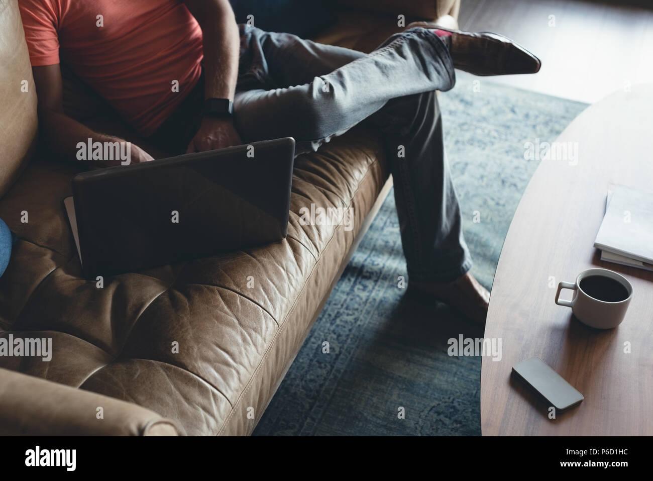 Businessman using laptop on a sofa Banque D'Images