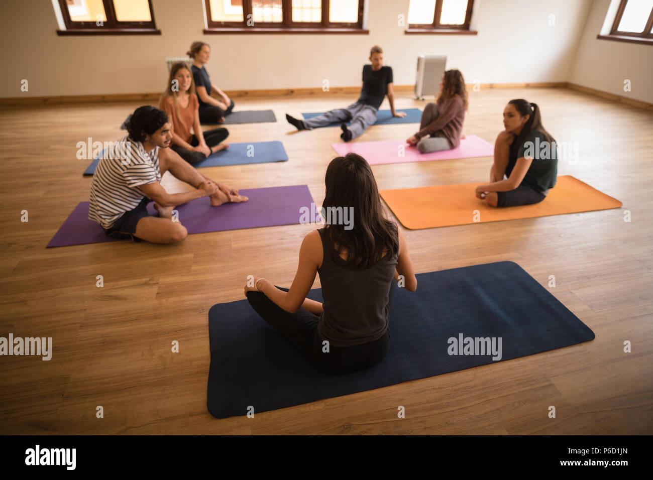 Female trainer en interaction avec un groupe de personnes Banque D'Images