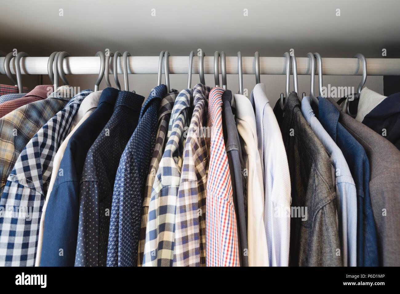 Divers shirts suspendus dans des cintres à la maison Banque D'Images