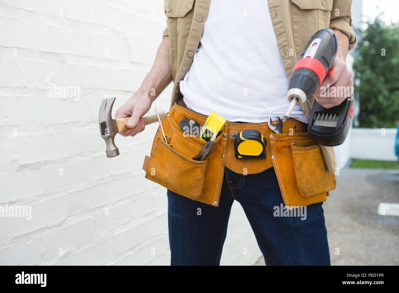 Male carpenter avec ceinture d'outils holding hammer et drill machine Banque D'Images
