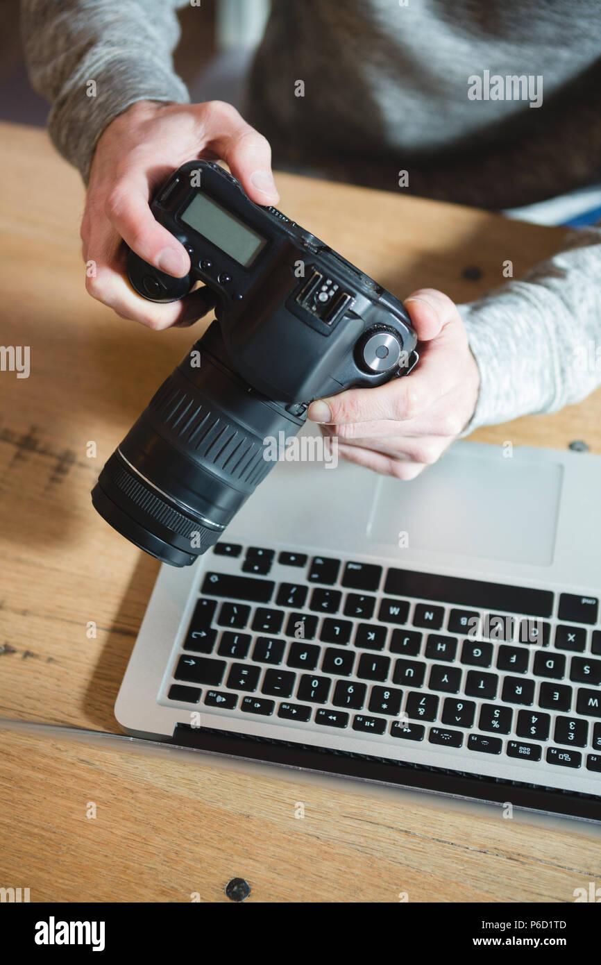 L'homme à l'aide d'un appareil photo numérique à la maison Banque D'Images