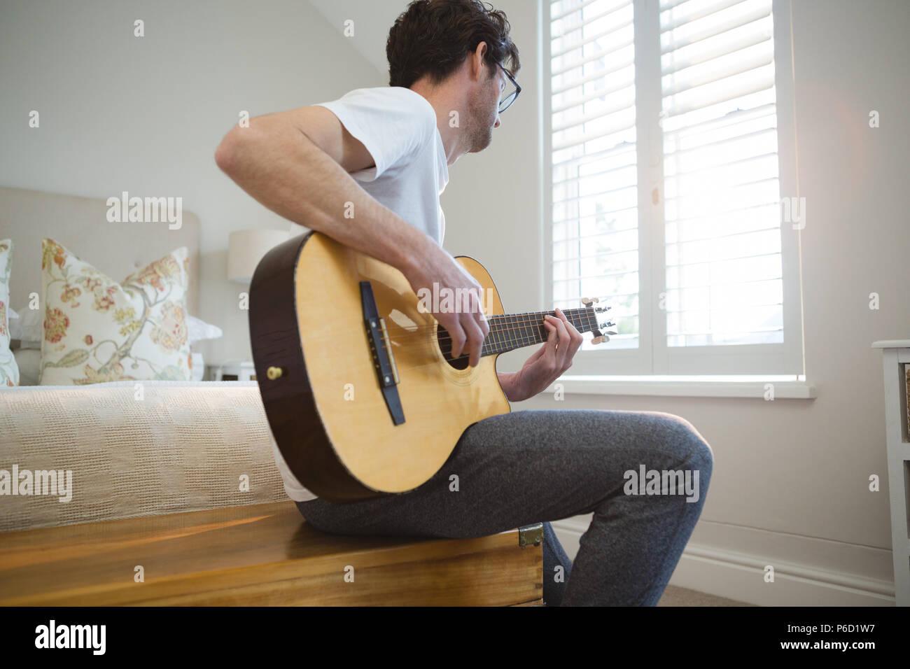 L'homme qui joue de la guitare dans la chambre Banque D'Images