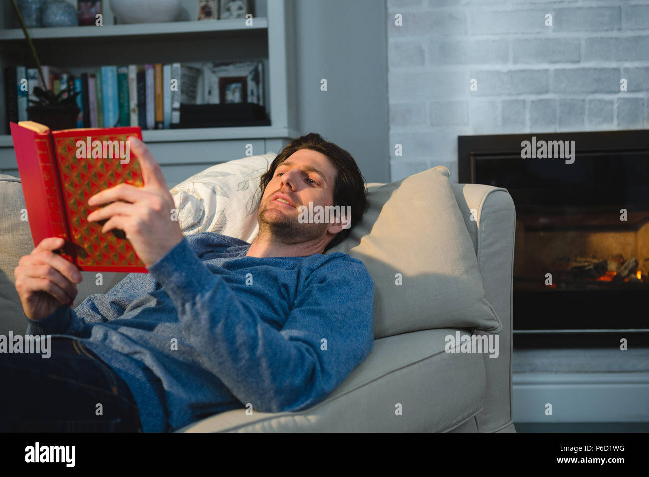 Man reading a book while lying on sofa in living room Banque D'Images