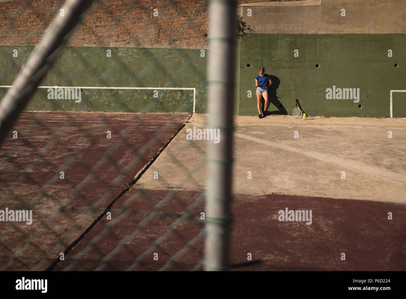 Woman leaning against wall dans la cour de tennis Banque D'Images