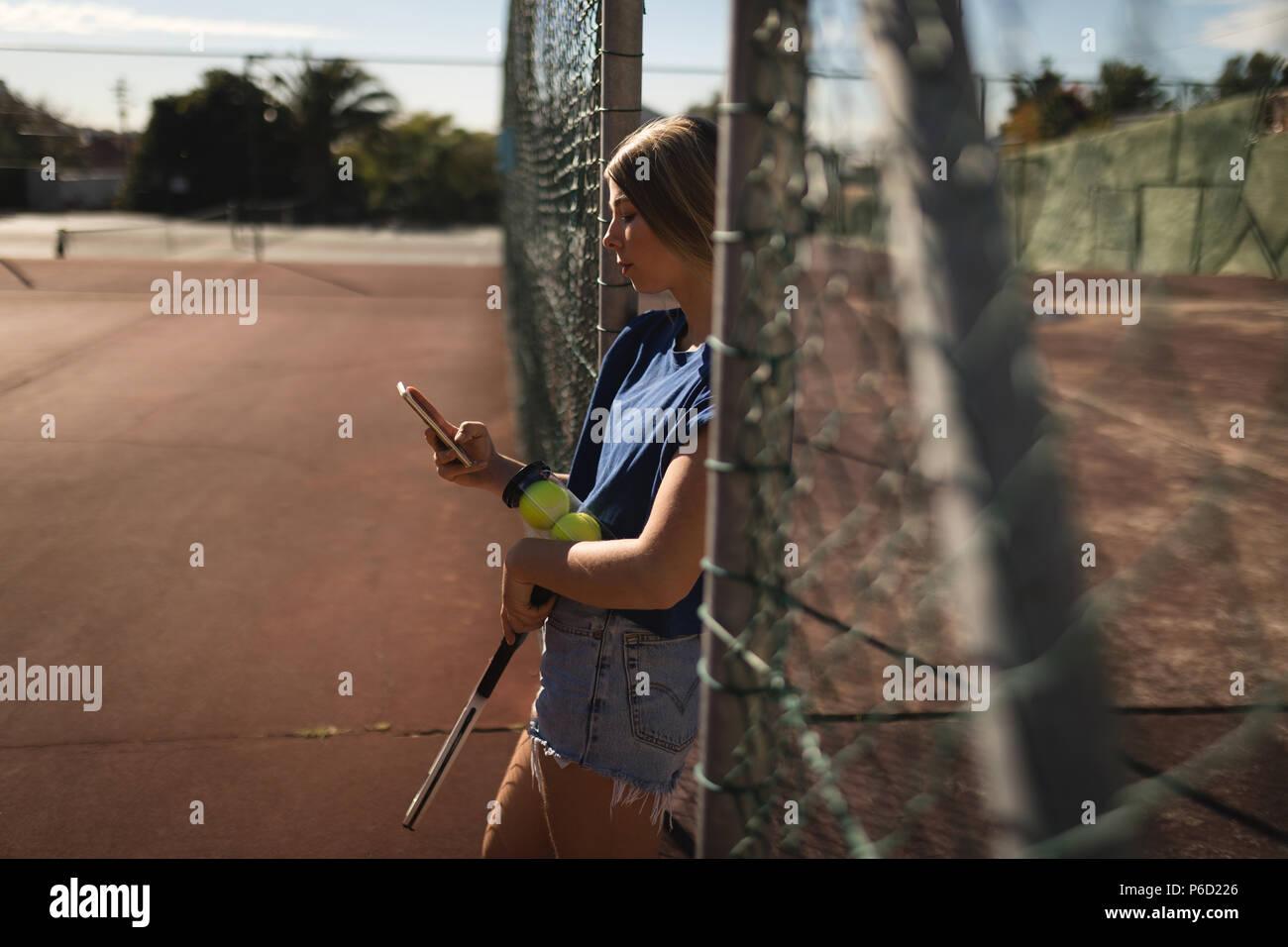 Femme à l'aide de téléphone mobile dans la cour de tennis Banque D'Images