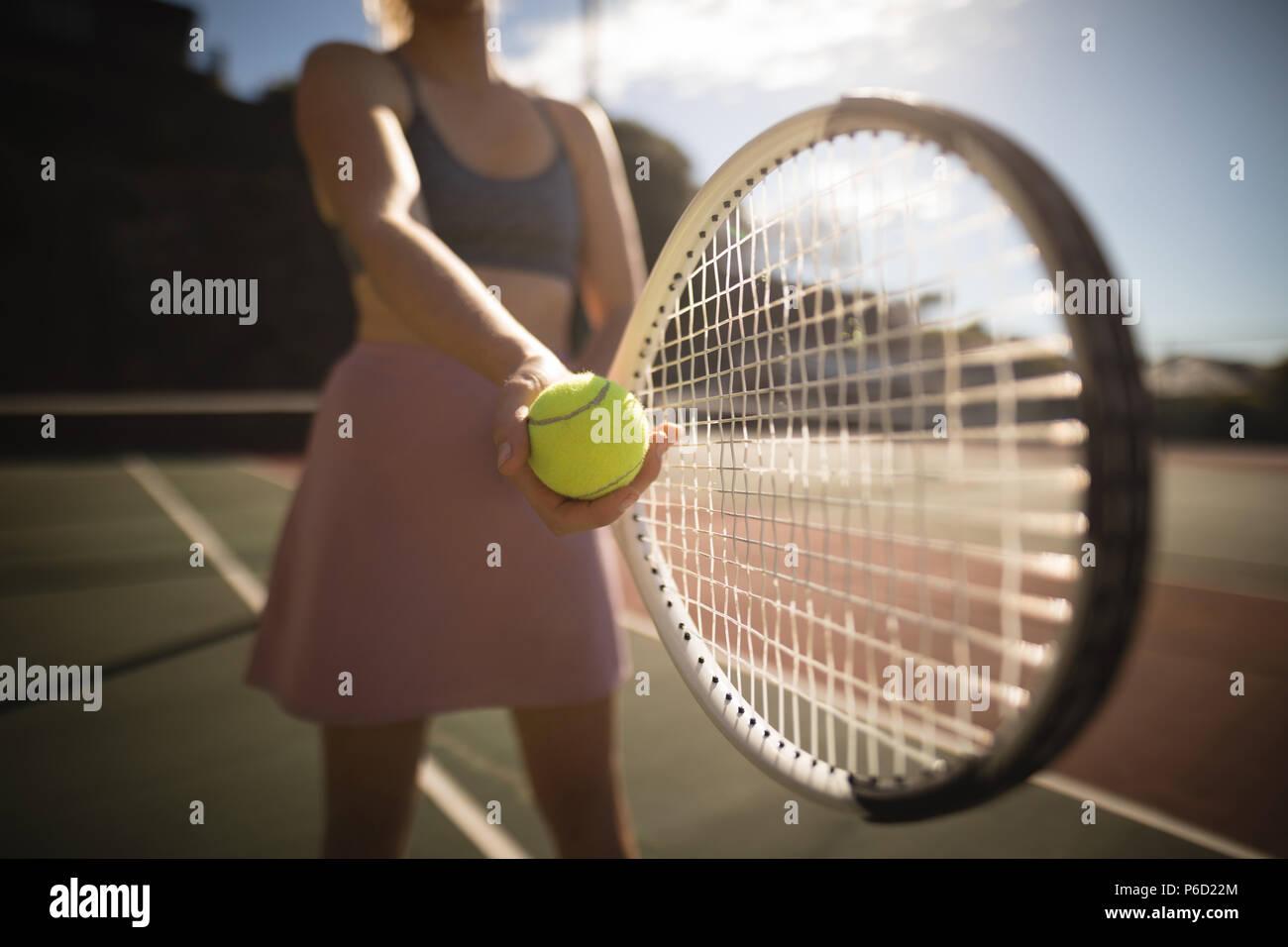 Femme pratiquant le tennis dans le court de tennis Banque D'Images
