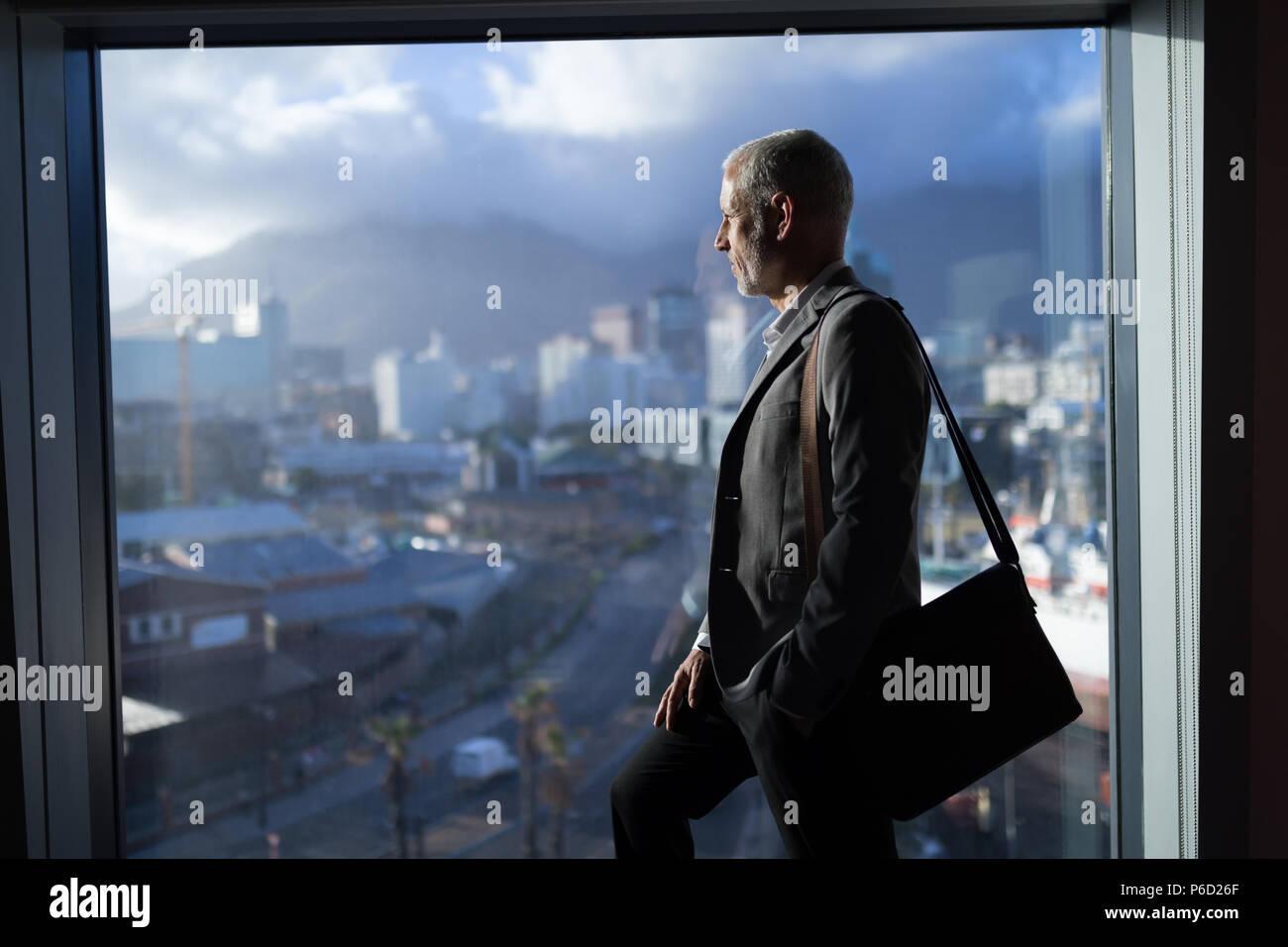 L'homme d'affaires à l'extérieur de la fenêtre Banque D'Images