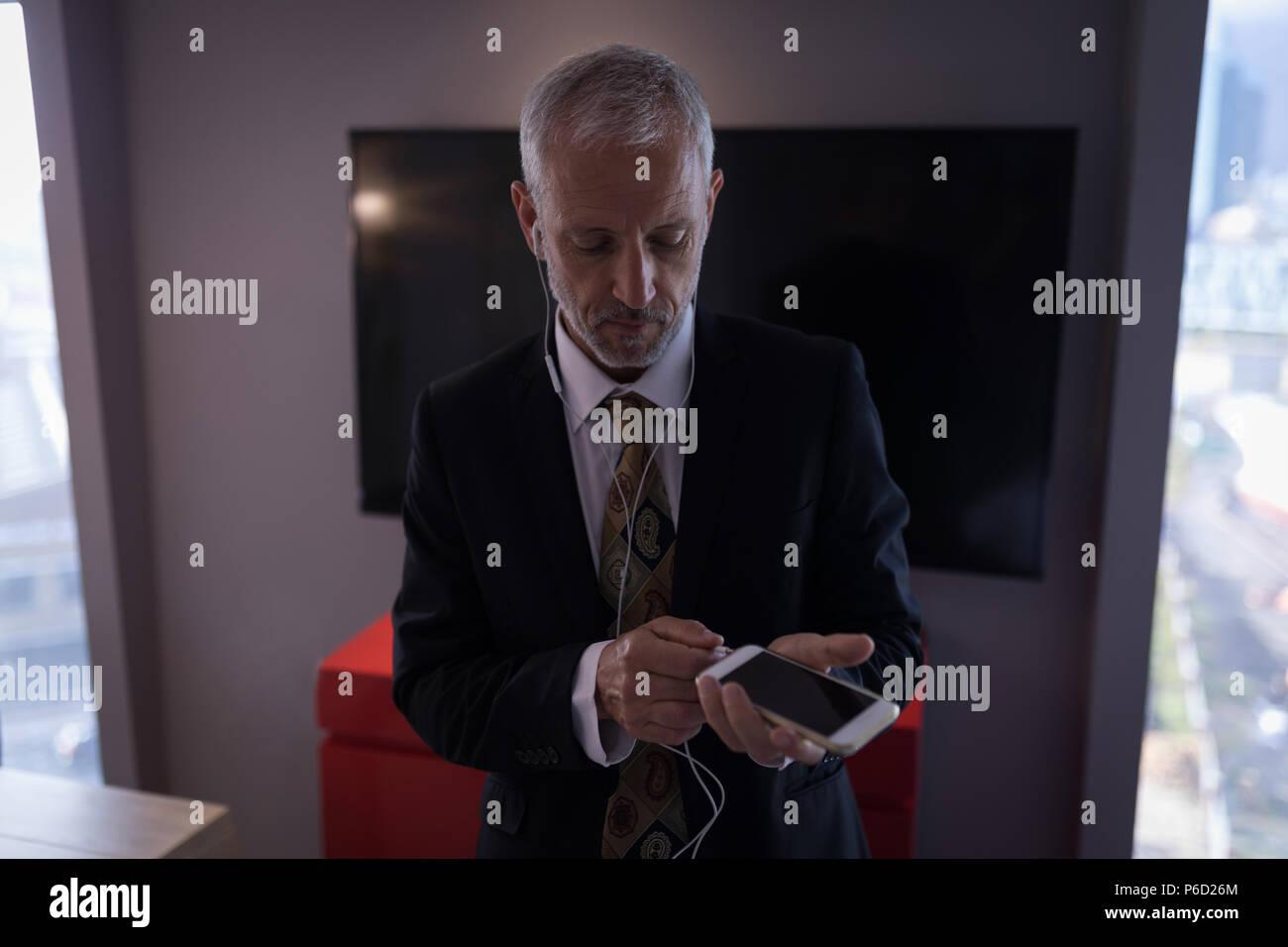 Businessman de brancher les écouteurs dans smart phone Banque D'Images