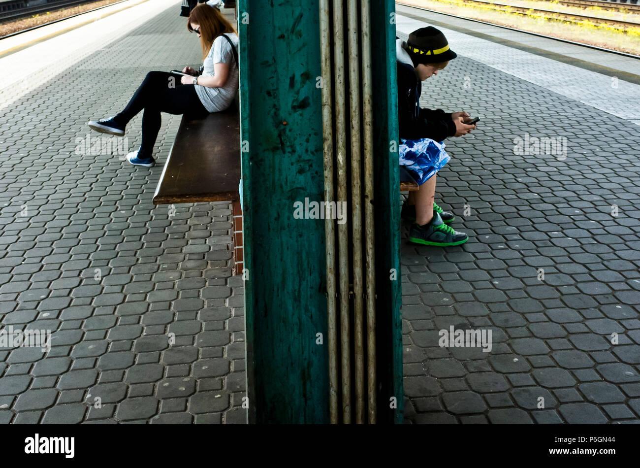 Un garçon et une fille assise sur un banc d'une gare ferroviaire de la plate-forme, train en attente et texting on smartphone Photo Stock