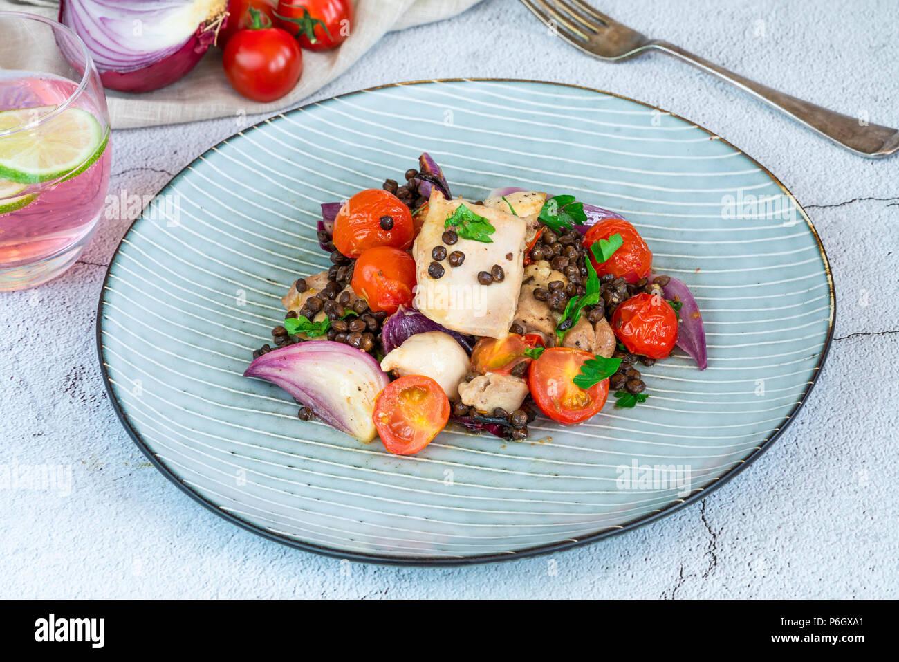 Le poulet et faire cuire les tomates cerise avec des lentilles du Puy Photo Stock