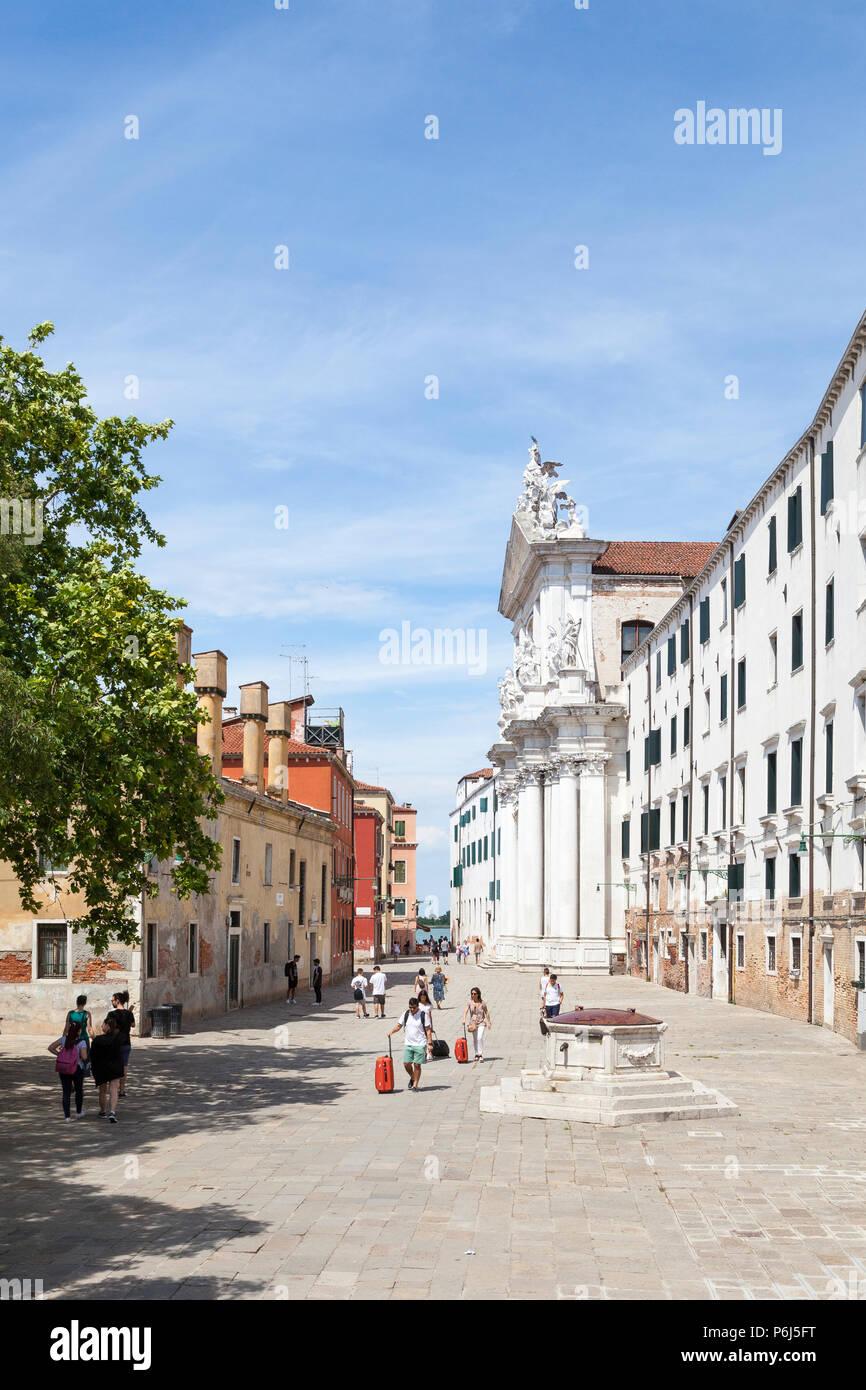 Refugee Église, Campo dei Gesuiti, Cannaregio, Venise, Vénétie, Italie avec les touristes à marcher avec assurance en passant l'ancien pozzo (tête de puits) Photo Stock