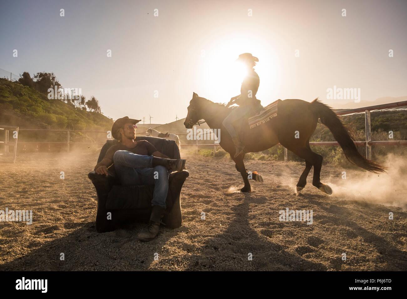 Les cavaliers avec les chevaux dans le coucher du soleil doré de lumière. Un homme assis sur un vieux fauteuil et une femme ride autour de lui rendre la poussière. image paysage avec moulins à vent dans la région de b Photo Stock