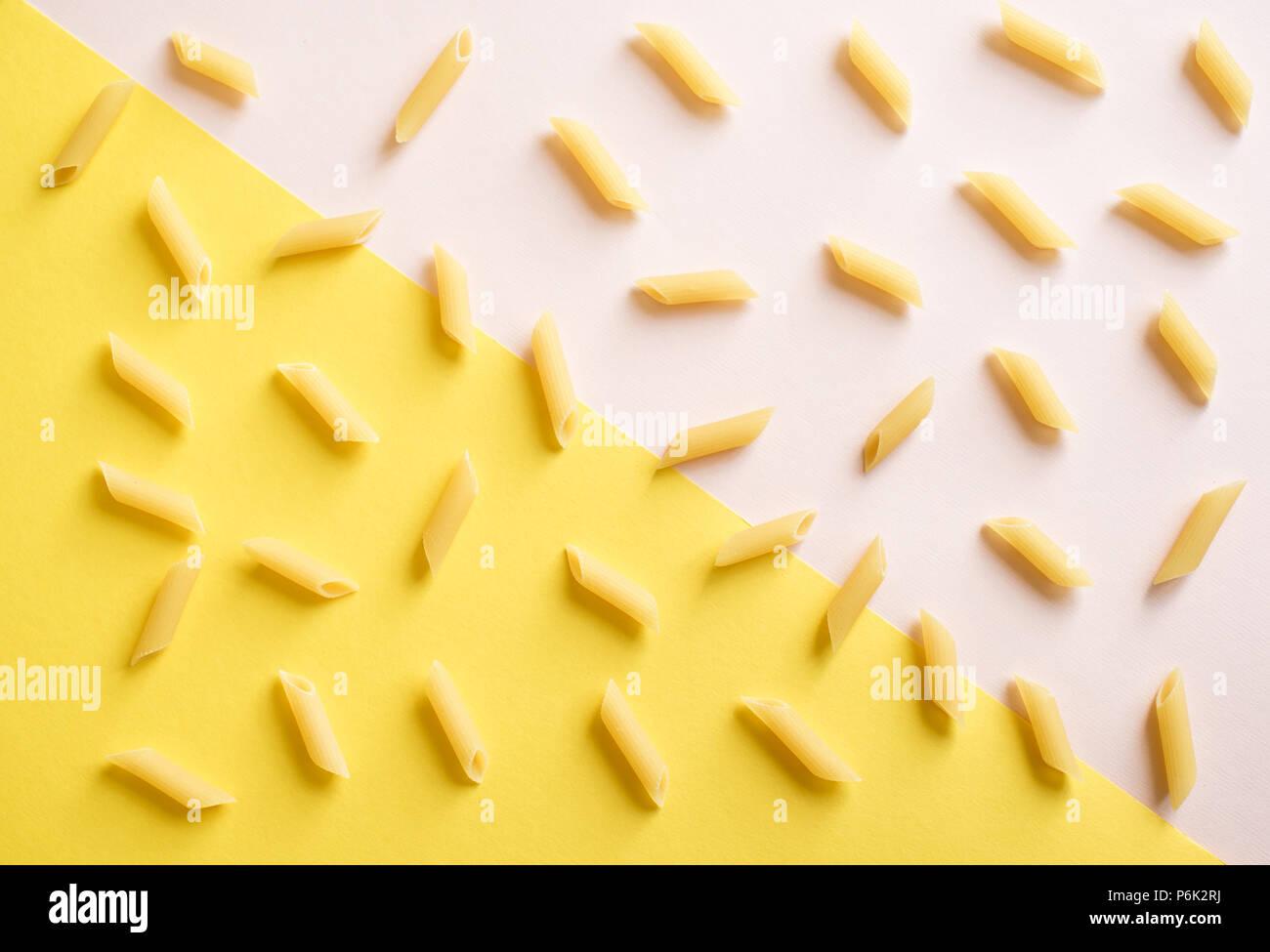 Pâtes penne rose sur fond jaune pastel et haut, vue, télévision lay. Photo Stock