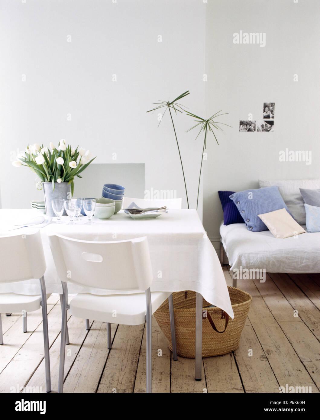 Exceptionnel Linge Blanc Et Du0027un Vase De Tulipes Blanches Sur Une Table Avec Des Chaises  En Plastique Blanc Dans Un Milieu Urbain Salle à Manger Avec Parquet Au Sol