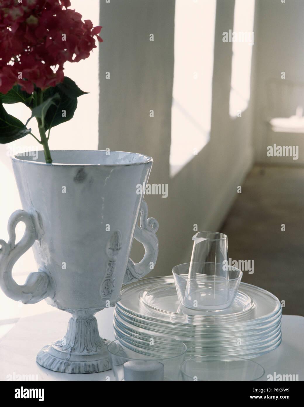 Close-up d'origine en céramique blanche vase à côté pile de plaques de verre Banque D'Images