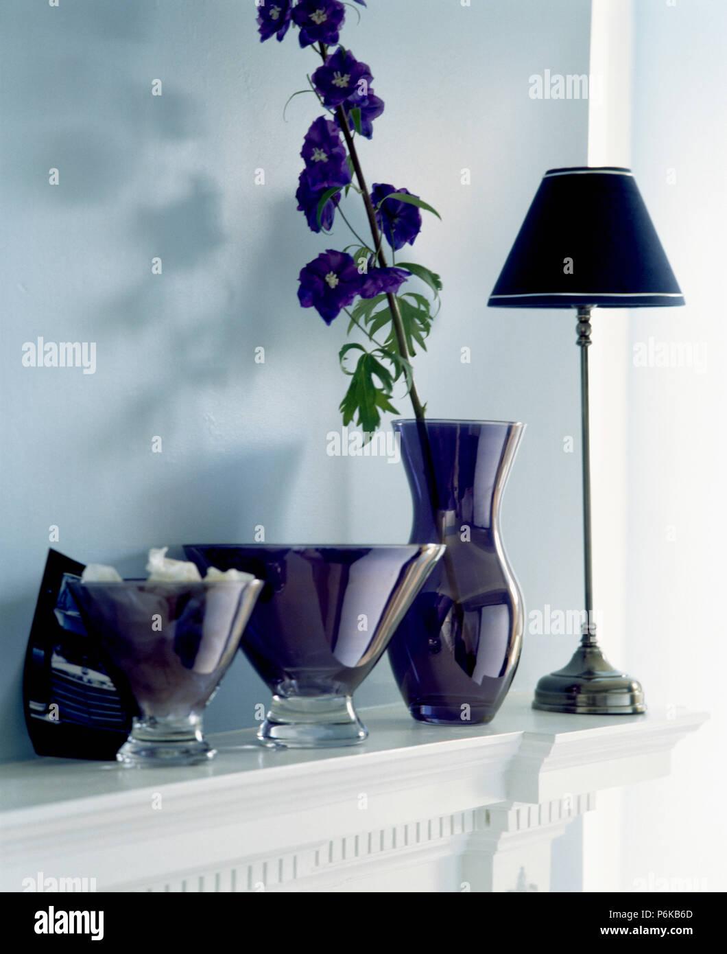 Close-up de pourpre foncé provenait des vases et grand vase avec delphinium bleu unique sur la cheminée avec lampe noire Banque D'Images