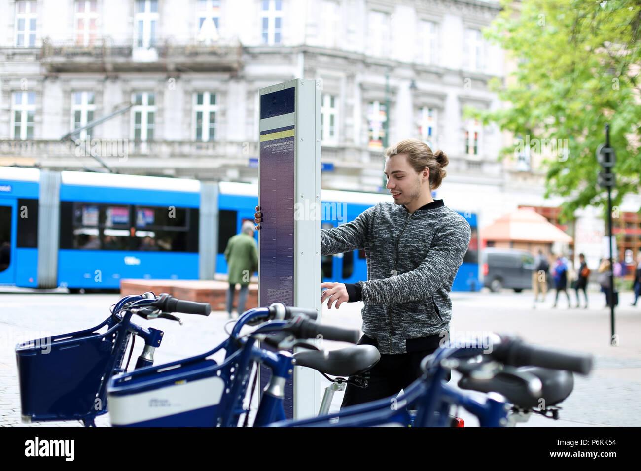 Jeune garçon en vélo, avec l'embauche de la machine en ville, route et trafic piétons en arrière-plan. Photo Stock