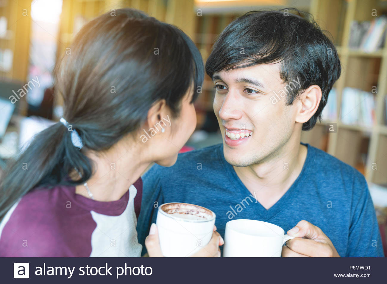 Jeune couple sympathique est de boire du café et souriant alors qu'il était assis au café Photo Stock