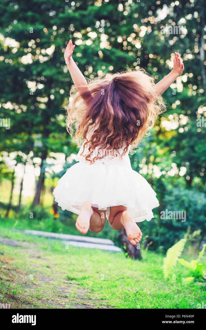 Belle petite fille saute en dehors de l'été au coucher du soleil Photo Stock