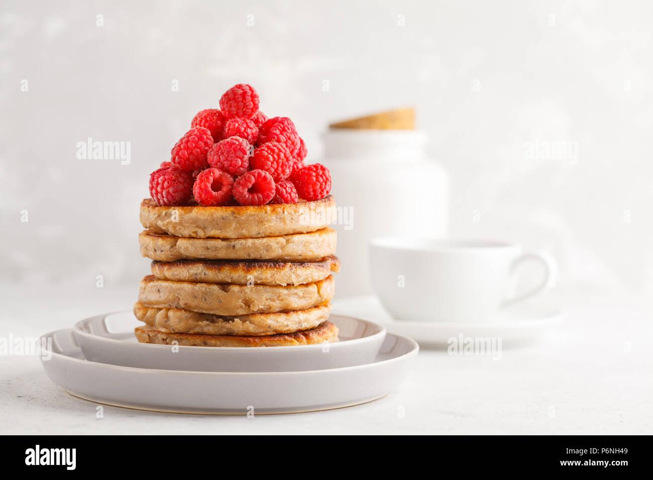 Crêpes végétaliennes de framboises et chia graines sur une assiette blanche, fond blanc. La nourriture végétalienne saine concept. Photo Stock