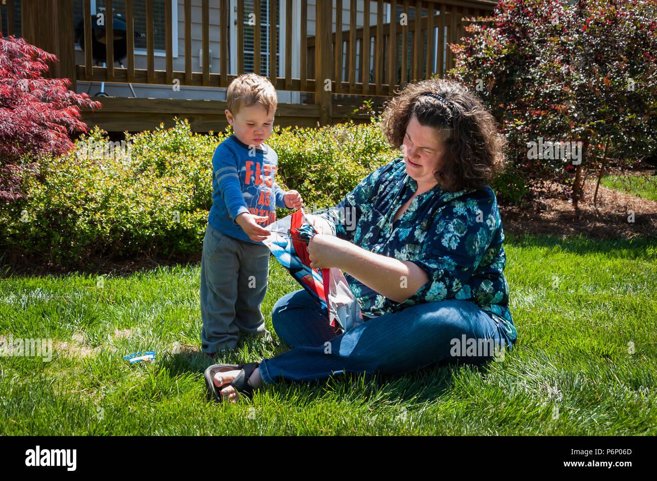Charlotte, NC-Avril 17, 2016: Jeune garçon regarde sa mère monter un cerf-volant dans la cour. Mère est assise dans l'herbe alors que le jeune fils tient sa main. Photo Stock