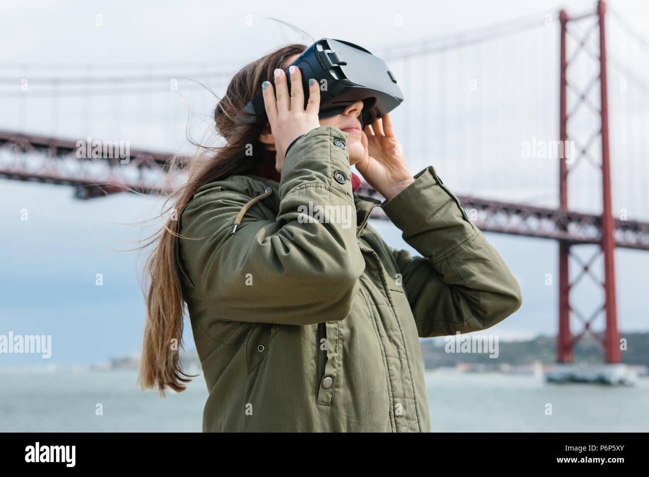 Belle jeune fille portant des lunettes de réalité virtuelle. Pont du 25 avril à Lisbonne dans l'arrière-plan. Le concept de technologies modernes et leur utilisation dans la vie quotidienne Photo Stock