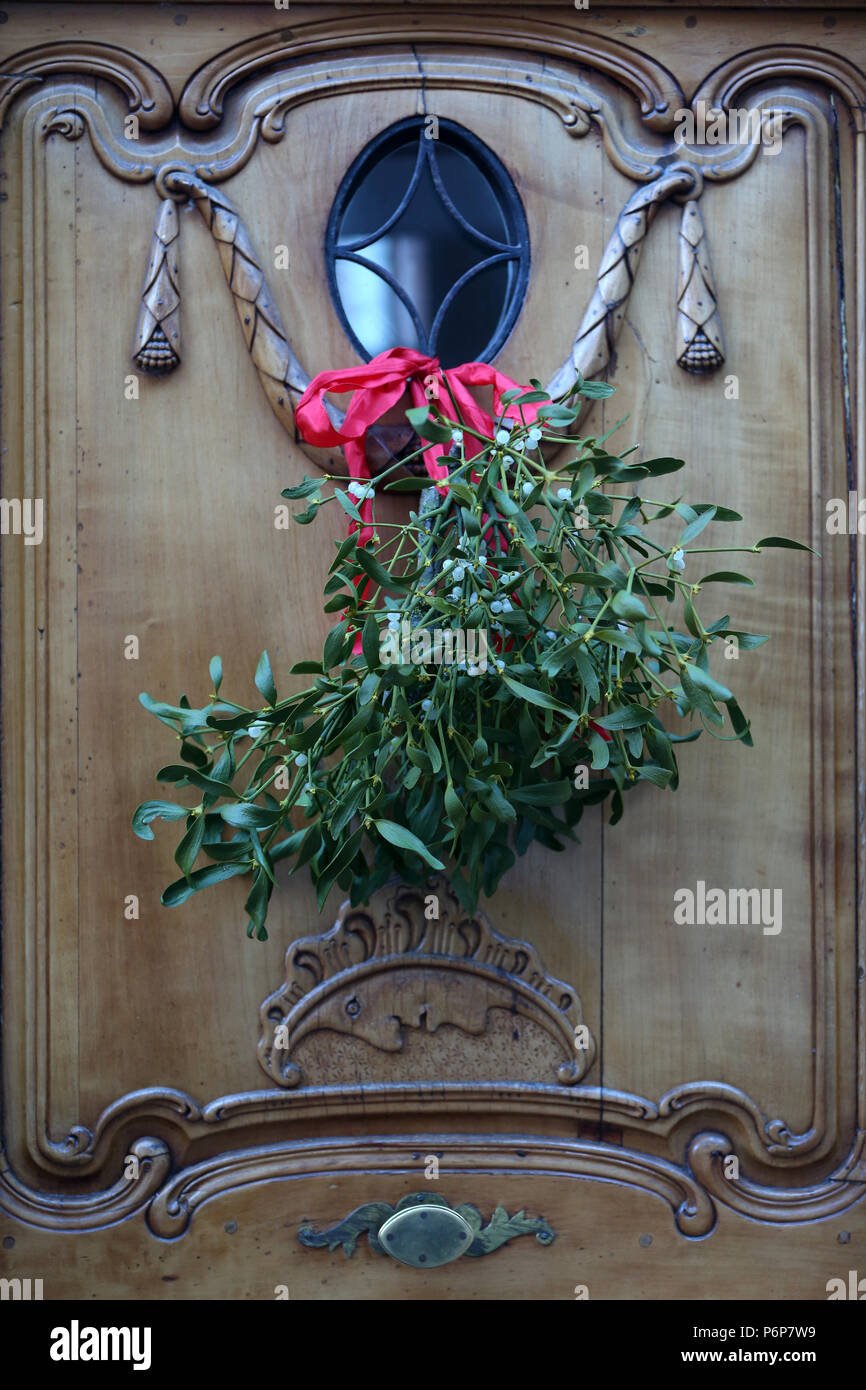 Décoration de Noël. Bouquet de gui (Viscum album) accroché sur la porte en bois. Bâle. La Suisse. Photo Stock